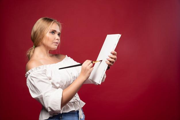 Blonder kunstmeister, der mit einem pinsel auf leinwand arbeitet und überrascht die person oder die natur ansieht. Kostenlose Fotos