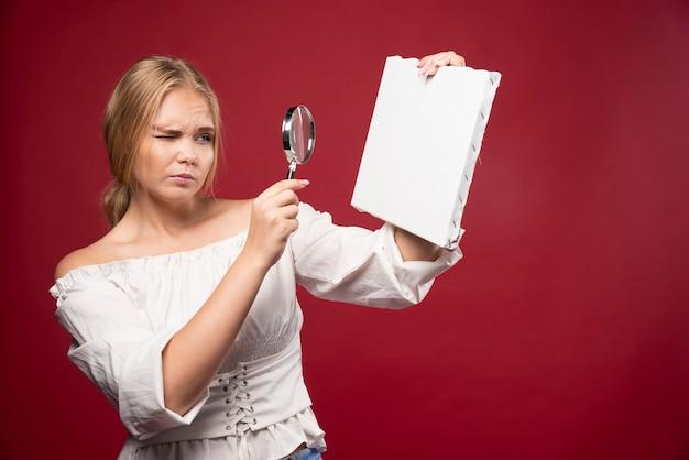 Blonder kunstmeister überprüft die leinwand mit einer lupe und sieht zweifelhaft aus.