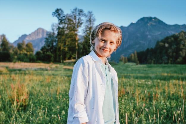 Blonder lächelnder junge, der kamera auf hintergrund der wunderbaren ansicht der grünen wiese und der berge, familienreiseabenteuerlebensstil betrachtet