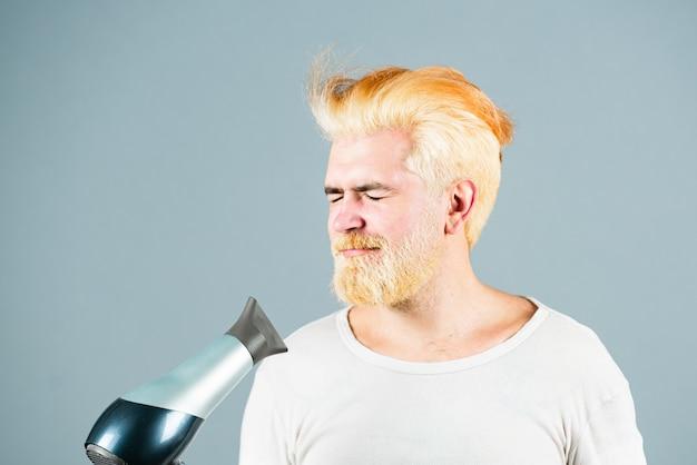 Blonder lustiger bärtiger mannhaartrockenhaarpflegemann lokalisiert