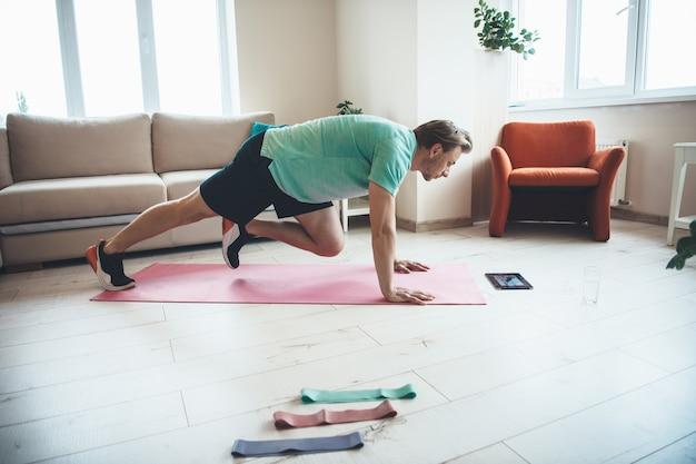 Blonder mann benutzt ein tablet, während er zu hause auf einer yogamatte fitnessübungen macht