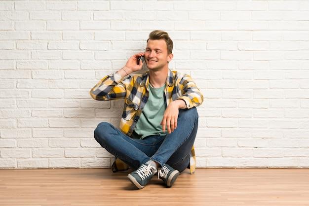 Blonder mann, der auf dem boden hält ein gespräch mit dem handy sitzt