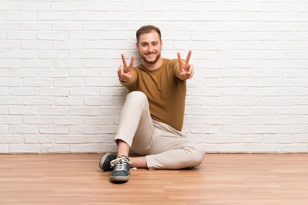 Blonder mann, der auf dem boden lächelt und siegeszeichen zeigt sitzt