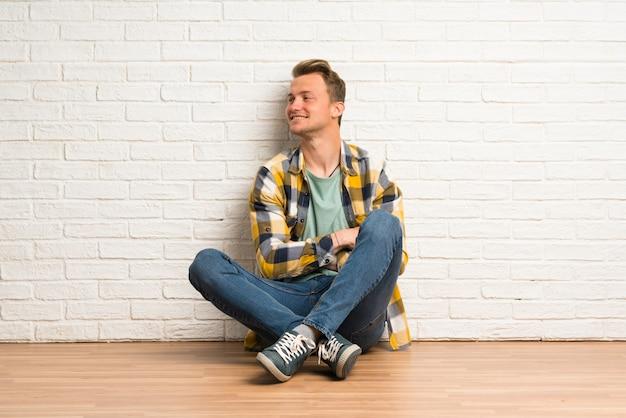 Blonder mann, der auf dem boden mit den armen gekreuzt und glücklich sitzt
