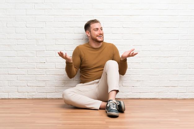 Blonder mann, der auf dem boden mit überraschungsgesichtsausdruck sitzt
