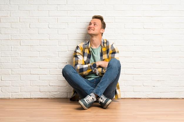 Blonder mann, der auf dem boden oben schaut beim lächeln sitzt