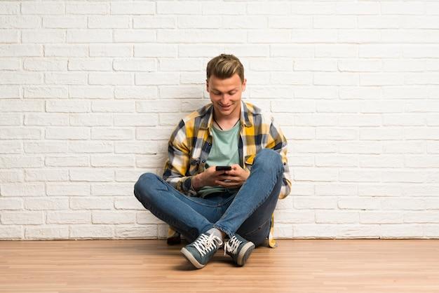 Blonder mann, der auf dem boden sendet eine mitteilung mit dem mobile sitzt