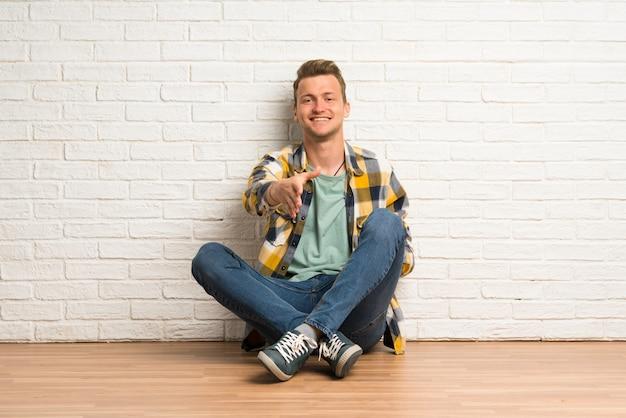 Blonder mann, der auf dem boden sitzt und hände schüttelt, weil er ein gutes geschäft gemacht hat