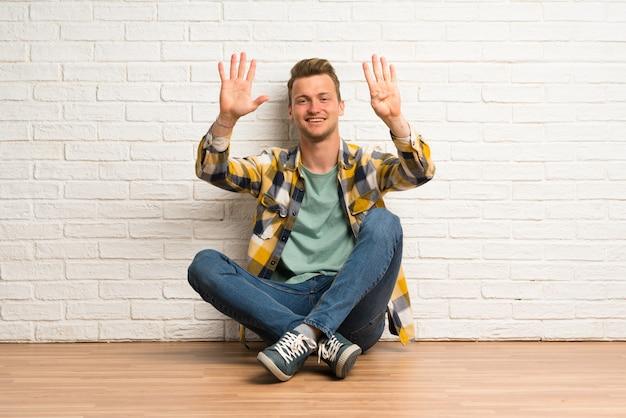 Blonder mann, der auf dem boden zählt neun mit den fingern sitzt