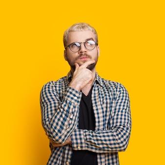 Blonder mann, der durch brillen schaut, während er sein kinn berührt und an etwas auf einer gelben wand mit freiem raum denkt