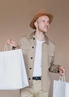 Blonder mann, der einkaufstaschen hält