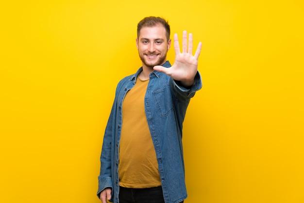 Blonder mann, der fünf mit den fingern zählt