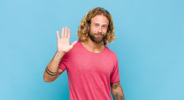 Blonder mann, der glücklich und fröhlich lächelt, hand winkt, sie begrüßt und begrüßt oder sich verabschiedet