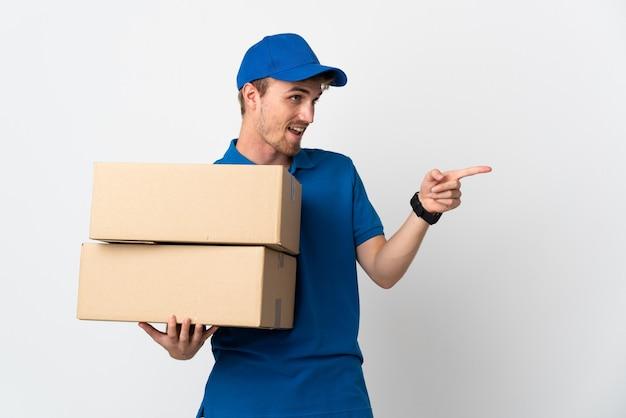 Blonder mann der jungen lieferung lokalisiert auf weißer wand, die finger zur seite zeigt und ein produkt präsentiert