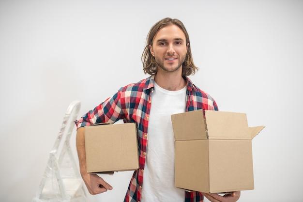 Blonder mann, der kisten in den händen hält und lächelt