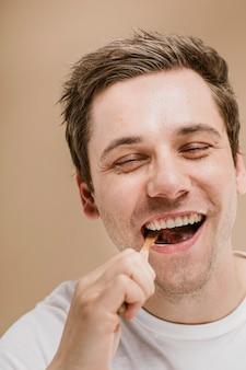 Blonder mann, der seine zähne mit einer hölzernen zahnbürste putzt