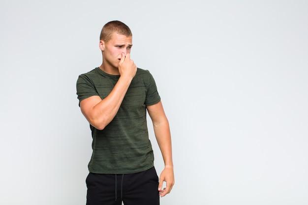 Blonder mann, der sich angewidert fühlt und die nase hält, um einen üblen und unangenehmen gestank zu vermeiden