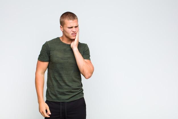 Blonder mann, der wange hält und schmerzhafte zahnschmerzen leidet, sich krank, elend und unglücklich fühlt und einen zahnarzt sucht