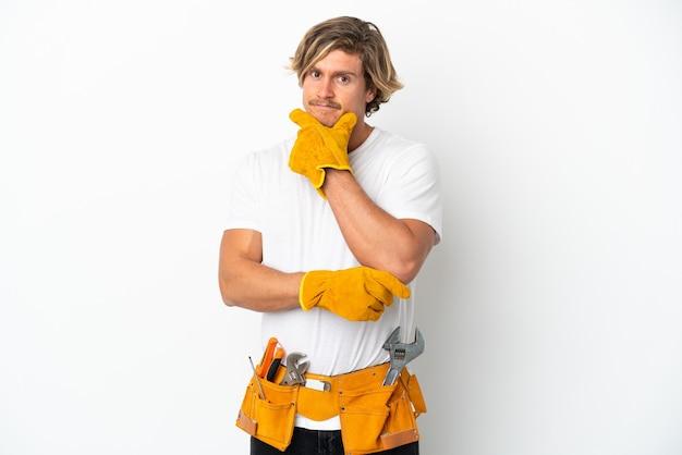 Blonder mann des jungen elektrikers lokalisiert auf weißem hintergrund denken
