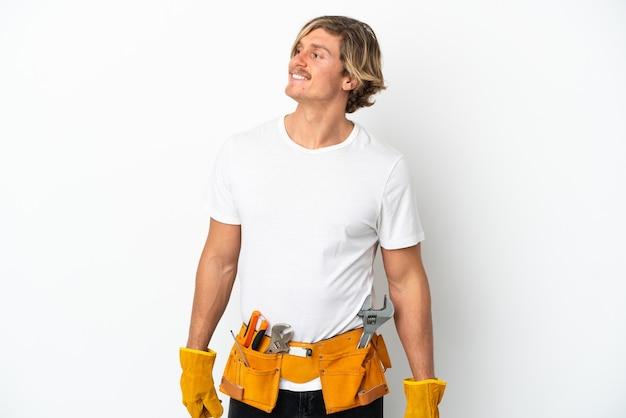 Blonder mann des jungen elektrikers lokalisiert auf weißem hintergrund, der zur seite schaut und lächelt