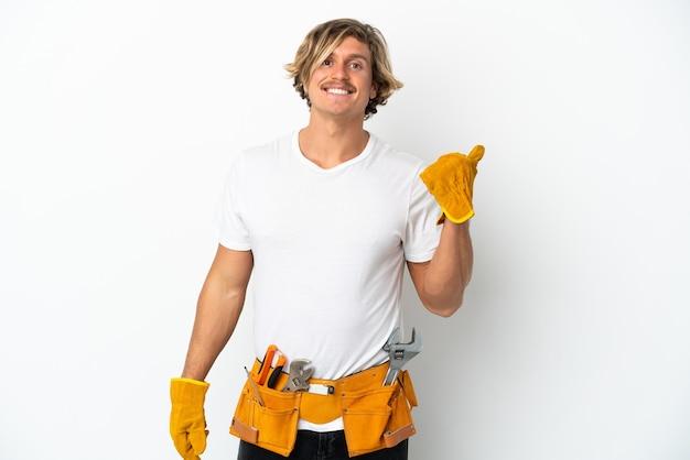 Blonder mann des jungen elektrikers lokalisiert auf weißem hintergrund, der zur seite zeigt, um ein produkt zu präsentieren