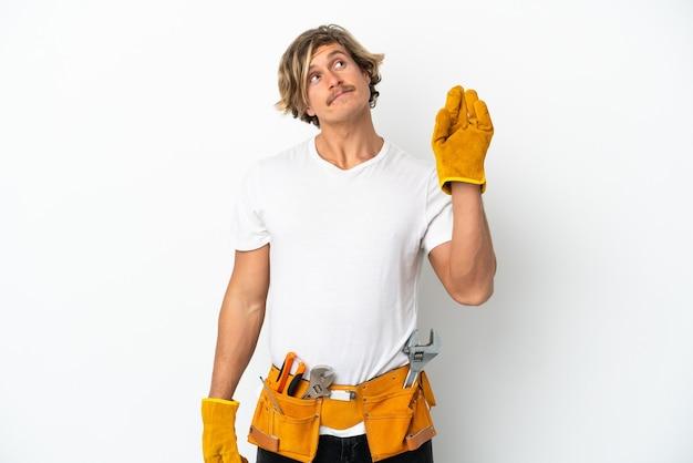 Blonder mann des jungen elektrikers lokalisiert auf weißem hintergrund mit den fingern, die das beste kreuzen und wünschen