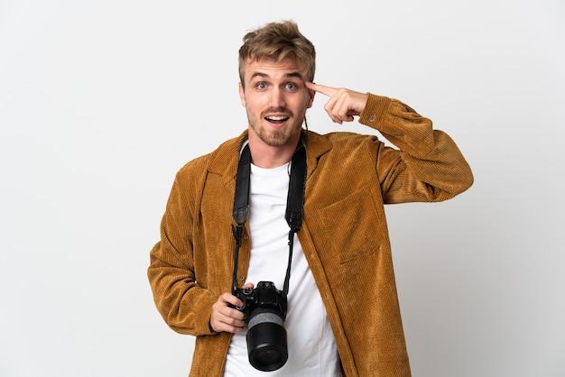 Blonder mann des jungen fotografen lokalisiert auf weißem hintergrund, der beabsichtigt, die lösung zu realisieren