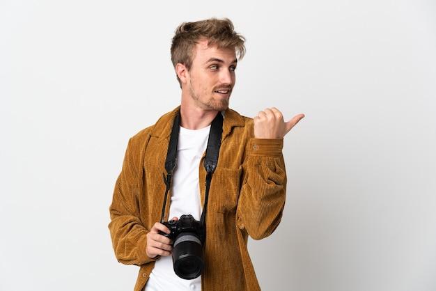 Blonder mann des jungen fotografen lokalisiert auf weißem hintergrund, der zur seite zeigt, um ein produkt zu präsentieren