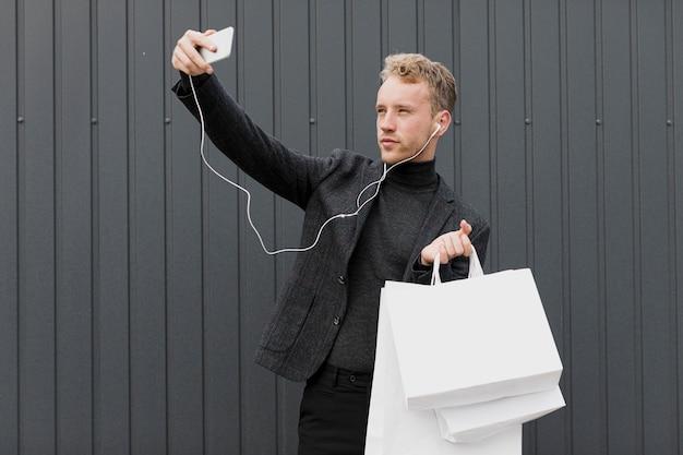 Blonder mann im schwarzen, der ein selfie mit smartphone nimmt
