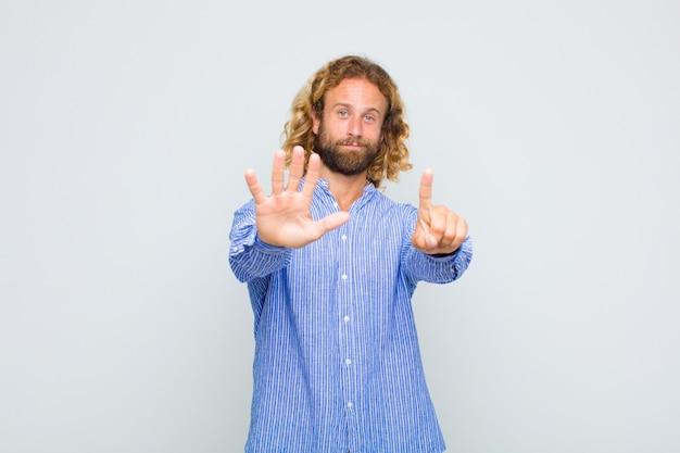 Blonder mann lächelt und sieht freundlich aus, zeigt nummer sechs oder sechste mit der hand nach vorne, countdown