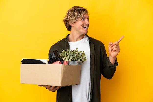 Blonder mann macht eine bewegung, während er eine kiste voller dinge aufhebt, die auf gelber wand isoliert sind, um die lösung zu realisieren, während er einen finger anhebt