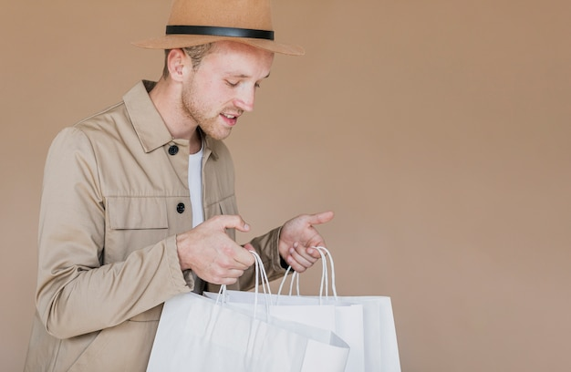 Blonder mann mit braunem hut und einkaufsnetzen