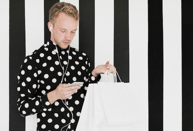 Blonder mann mit dem hemd, das den smartphone betrachtet