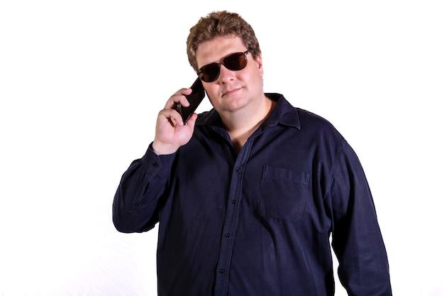 Blonder mann mit sonnenbrille, die auf smartphone lokalisiert auf weißer wand spricht