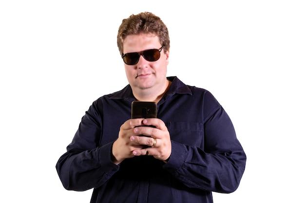 Blonder mann mit sonnenbrille, die nachricht auf smartphone lokalisiert auf weißer wand sendet