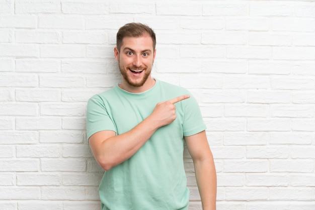 Blonder mann über backsteinmauer finger auf die seite zeigend