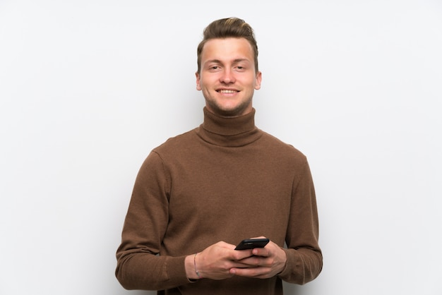 Blonder mann über der lokalisierten weißen wand, die eine mitteilung mit dem mobile sendet