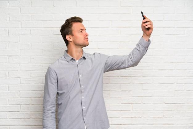 Blonder mann über der weißen backsteinmauer, die ein selfie macht