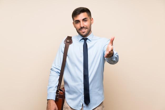 Blonder mann über lokalisiertem weißem wandverkleidungsmund mit den händen