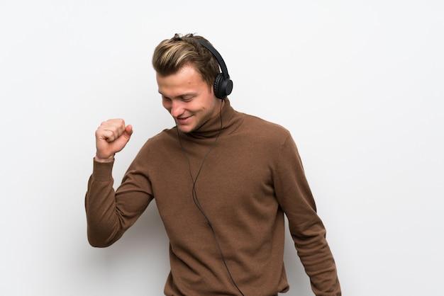 Blonder mann über lokalisierter weißer wand hörend musik mit kopfhörern und tanzen