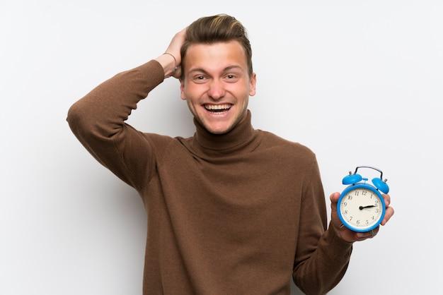 Blonder mann über lokalisierter weißer wand unruhig, weil es spät geworden ist und weinlesewecker hält