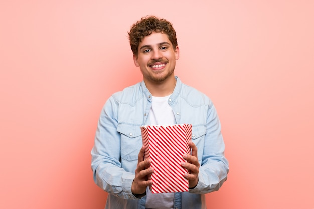 Blonder mann über rosa wand popcorn essend