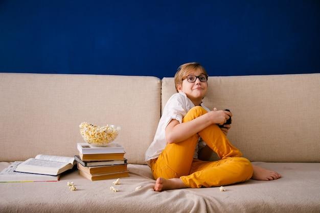 Blonder schuljunge mit brille spielt videospiele, hält ein gamepad, isst popcorn