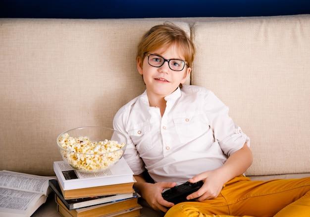 Blonder schuljunge mit brille spielt videospiele, hält ein gamepad