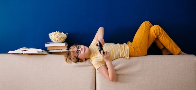 Blonder schuljunge spielt videospiele, hält ein gamepad, isst popcorn