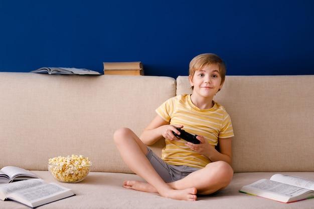 Blonder schuljunge spielt videospiele, hält ein gamepad