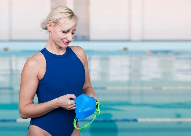 Blonder schwimmer, der badekappe hält