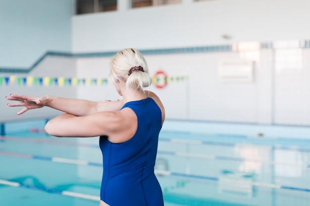 Blonder schwimmer, der zurück schuss ausdehnt