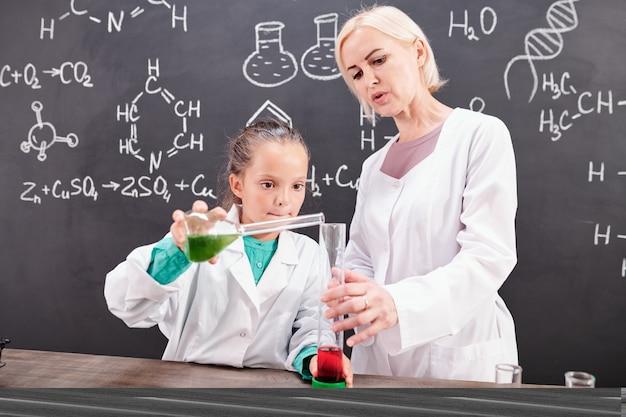 Blonder selbstbewusster chemielehrer, der ein schulmädchen im weißen kittel betrachtet, das grüne flüssige substanz in der tube mit roter an der tafel vermischt