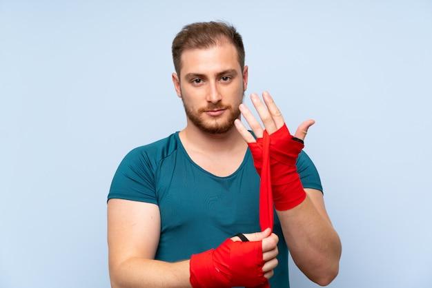 Blonder sportmann über blauer wand in den verpackenverbänden